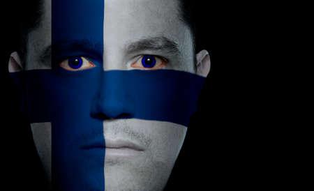 finland�s: Finland�s bandera pintada  proyecta sobre un hombre de la cara.  Foto de archivo