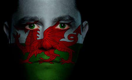 welsh flag: Bandiera gallese dipinte  proiettate su un volto di uomo.