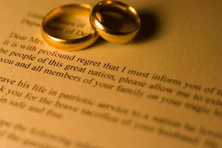 telegrama: Carta de condolencia a la esposa del soldado muerto en la guerra, con dos anillos de boda. Profundidad de campo y de colores c�lidos.