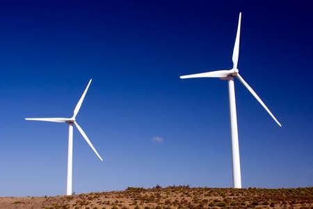 Two wind turbines standing in the savannah in western Algarve, Portugal. Stock Photo