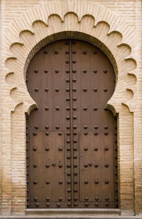 Medieval moorish-style door on a brick building in Toledo, Spain