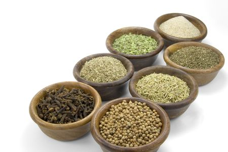 Small wooden bowls containing a number of herbs and spices: cloves, coriander, oregano, celery salt, crushed mint leaves, thyme and cumin