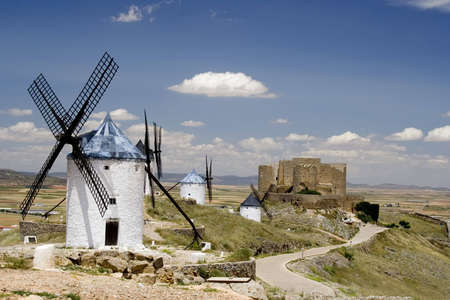 Medieval windmills dating from the 16th century on a hill overlooking the town of Consuegra in Toledo province, Castilla La Mancha, central Spain.  Made famous in Miguel de Cervantes Saavedra's novel Don Quijote de la Mancha, these windmills are situated Stock Photo - 1134633