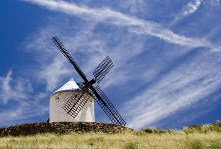 Medieval windmill dating from the 16th century on a hill overlooking the town of Consuegra in Toledo province, Castilla La Mancha, central Spain.  Made famous in Miguel de Cervantes Saavedra's novel Don Quijote de la Mancha, these windmills are situated a Stock Photo - 1134634