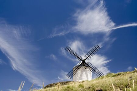 Medieval windmill dating from the 16th century on a hill overlooking the town of Consuegra in Toledo province, Castilla La Mancha, central Spain.  Made famous in Miguel de Cervantes Saavedra's novel Don Quijote de la Mancha, these windmills are situated a Stock Photo - 1173231