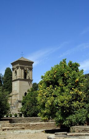 The tower of the Convento de San Francisco with an orange tree in the foreground - part of the La Alhambra complex in Granada, Spain. photo
