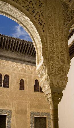 Mudejar arch in the Patio del Cuarto Dorado with the facade of the Palacio de Comares in the Alhambra, Granada Spain.