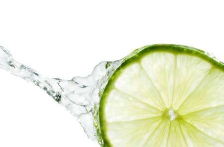 Crystal clear water splashing from a slice of lime.  Isolated on a white background. Stock Photo - 1342192