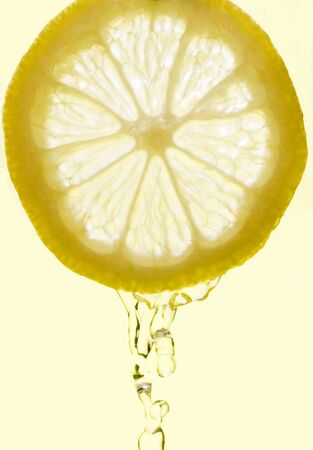 Crystal clear water splashing from a slice of lemon.  Isolated on a light yellow background. photo