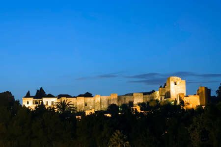View of the Alcazaba palace complex in Malaga, southern Spain at dusk.