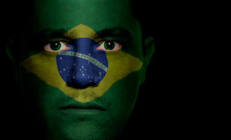 Brazilian flag painted/projected onto a man's face. Imagens - 1423576
