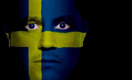 スウェーデンの国旗は、男の顔の塗装投影します。 写真素材