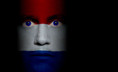 aggressor: Dutch flag paintedprojected onto a mans face. Stock Photo