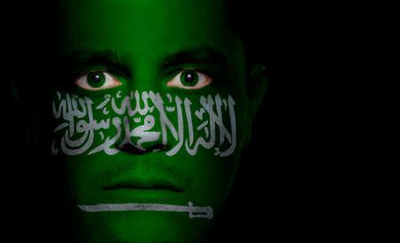 Saudi Arabian flag paintedprojected onto a mans face.
