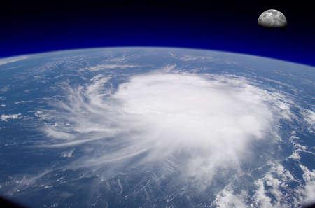 courtoisie: Vue de l'espace d'un g�ant de l'ouragan sur l'oc�an avec en arri�re-plan la lune. Photo montage avec des photos de courtoisie visibleearth.nasa.gov
