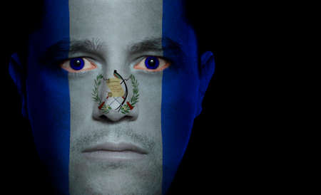 Guatemalan flag paintedprojected onto a mans face. Stock Photo