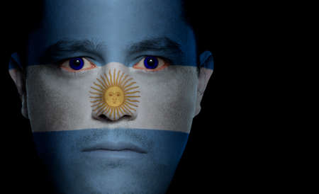 Argentinean flag paintedprojected onto a mans face. Stock Photo
