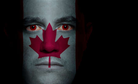Canadian flag paintedprojected onto a mans face. photo