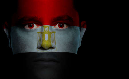 Egyptian flag paintedprojected onto a mans face.