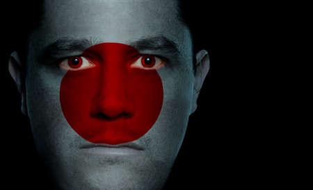 bandera japon: Japon�s bandera pintada  proyecta sobre un hombre de la cara.  Foto de archivo