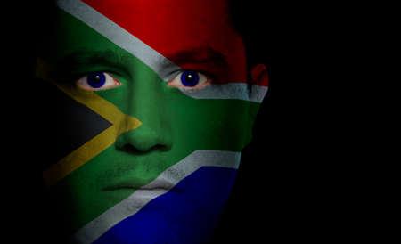 cara pintada: Sud�frica bandera pintada  proyecta sobre el rostro de un hombre.