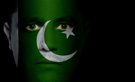 Pakistani flag painted/projected onto a man's face. photo