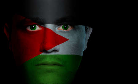 aggressor: Palestinean flag paintedprojected onto a mans face.