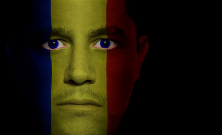 Romanian flag painted/projected onto a man's face. Stock Photo - 1674058