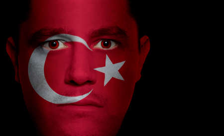 aggressor: Turkish flag paintedprojected onto a mans face.