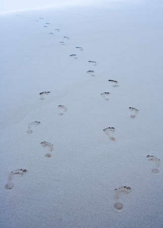 Footprints on a beach leading into the water. Banque d'images