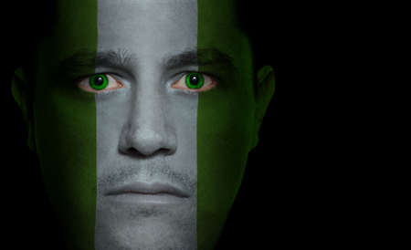 Nigerian flag painted/projected onto a man's face photo