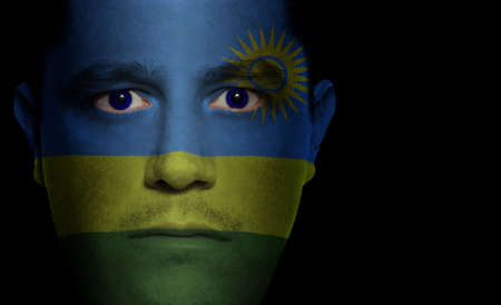 Rwandan flag painted/projected onto a man's face photo