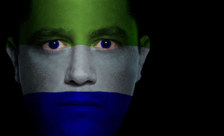 Sierra Leonese flag painted/projected onto a man's face photo