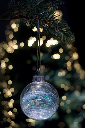 Clear glass Christmas ornament hanging from a tree with a background of blurred lights photo