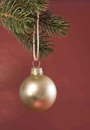 Golden glass Christmas ornament hanging from a tree with a shiny red background.