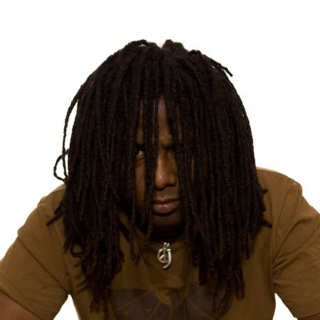 Serious African adult male with dreadlocks hanging in front of his face on a white background.