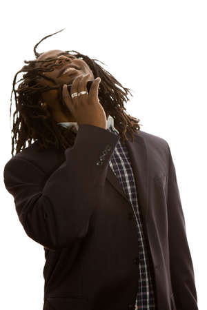 Smiling African adult male businessman with dreadlocks dressed in business casual talking on his mobile phone.