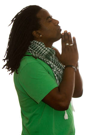 African adult male with dreadlocks standing in profile with hands in a prayer.