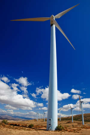 Wide angle view of a wind turbine with a blue sky and clouds. photo