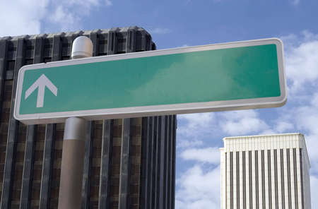Blank street sign with an arrow located in a business district.  Suitable for superimposing your own text.