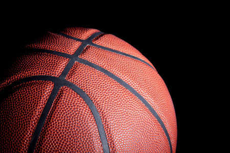 Close-up of a basketball with dramatic side lighting on a black background.