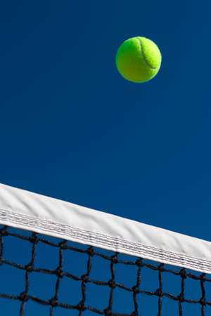 Close-up of a tennis ball going over the net with a blue sky background.