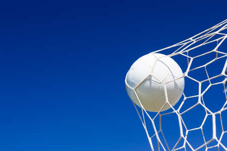 Close-up of a soccer ball (football) going into the back of the net with a blue sky background.