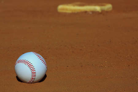 infield: Close-up of a baseball on the infield dirt of a baseball diamond with a base in the background.