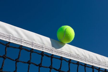 Close-up of a tennis ball touching the net tape with a blue sky background. Stock Photo