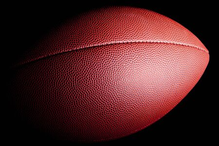 Close-up of an american football with dramatic side lighting on a black background.
