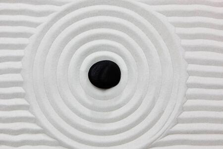 Gros plan sur une pierre noire sur fond blanc commissionnée sable dans un japonais ornementales ou un jardin zen. Banque d'images