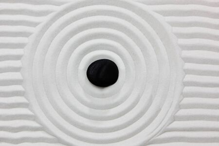Close-up of a black stone on white raked sand in a Japanese ornamental or zen garden. Banque d'images