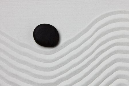 Close-up of a black stone on white raked sand in a Japanese ornamental or zen garden. Imagens