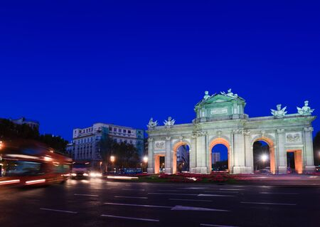 View of the Puerta de Alcal� in Madrid, Spain with lights of oncoming traffic.  It was commissioned by King Carlos III, with construction beginning in 1778. Stock Photo - 8418827